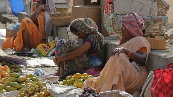 Indian fruit vendors wait for customers on a sidewalk in the shade of a tree on a hot summer day in Hyderabad, India, Thursday, May 28, 2015. Eating onions, lying in the shade and splashing into rivers, Indians were doing whatever they could Thursday to stay cool during a brutal heat wave that has killed more than 1,000 in the past month.