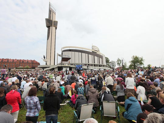 Thousands of faithful gathered in front of God's Mercy sanctuary in Krakow, Poland, Sunday, April 27, 2014, to attend a mass and watch live from the Vatican as Pope Francis declares Polish-born Pope John Paul II a saint. (AP Photo/Czarek Sokolowski)