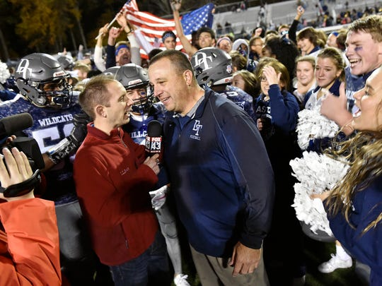 Surrounded by celebrating students and players, Dallastown head football coach Kevin Myers speaks with a reporter on the field after the Wildcats won a YAIAA football game Friday, Nov. 3, 2017, at Dallastown. Dallastown defeated Red Lion 40-27.