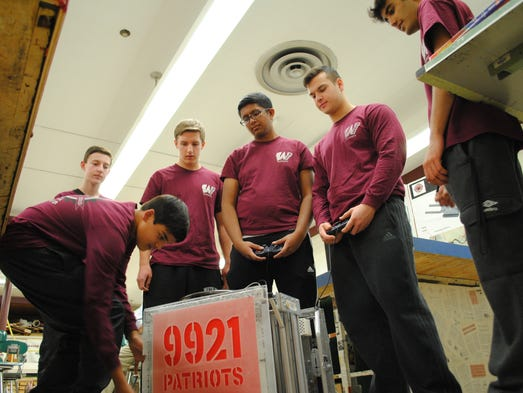 Team members make adjustments to their robot before