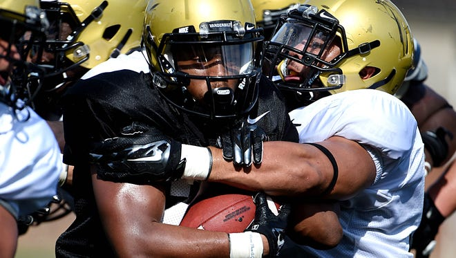 Vanderbilt running back Josh Crawford (22) is tackled by linebacker Darreon Herring (35) during the first day of full pads on Monday.