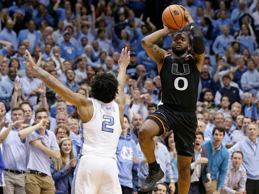 FILE - In this Feb. 27, 2018, file photo, Miami's Ja'Quan Newton (0) shoots the game-winning shot as time expires while North Carolina's Joel Berry II (2) defends during the second half of an NCAA college basketball game in Chapel Hill, N.C. Miami won 91-88. Newton has watched replays of his desperation shot to beat North Carolina countless times on screens large and small. It always goes in. (AP Photo/Gerry Broome, File)