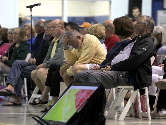 Mark McConnell, center, waits for the next speaker