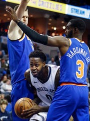 Memphis Grizzlies forward JaMychal Green (middle) splits the defense of New York Knicks teammates Kristaps Porzingis (left) and Tim Hardaway Jr. (right) during second quarter action at the FedExForum in Memphis, Tenn., Wednesday, January 17, 2018.