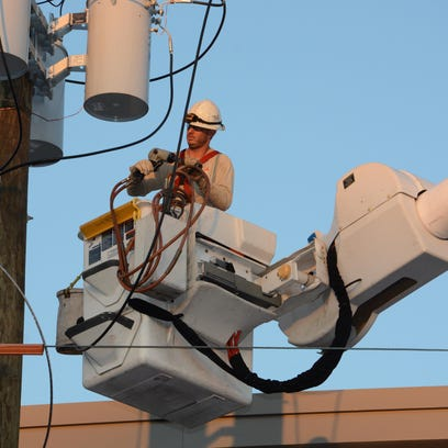 A Gulf Power lineman performs work in the downtown