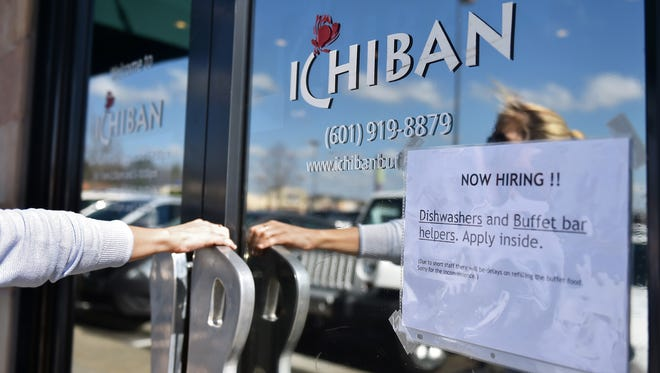 A patron walks into Ichiban Friday in Flowood, two days after 55 people were detained in multiple raids at Mississippi restaurants.
