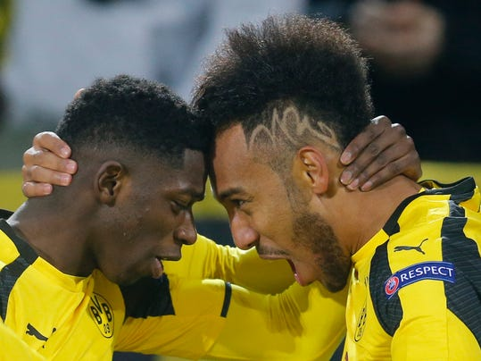 FILE - In this March 8, 2017 file photo Dortmund's Ousmane Dembele, left, congratulates Dortmund's Pierre-Emerick Aubameyang as they celebrate after scoring the opening goal during the Champions League round of 16, second leg, soccer match between Borussia Dortmund and Benfica in Dortmund, Germany. The big-money moves of Dembele and now Aubameyang underline a crisis of identification at Borussia Dortmund. Both players forced their way out of the club after feeling the need to move onto bigger and better stages to showcase their talents. (AP Photo/Michael Probst)