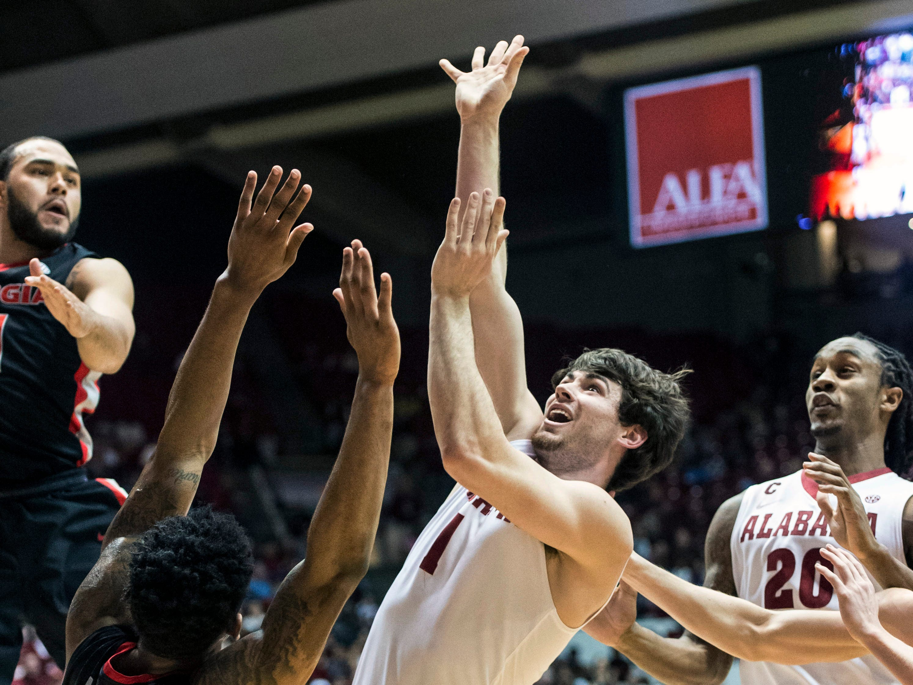 Alabama guard/forward Riley Norris (1) goes inside for two as Georgia guard Charles Mann defends during an NCAA college basketball game, Saturday, Feb. 21, 2015, at Coleman Coliseum in Tuscaloosa, Ala. (AP Photo/AL.com, Vasha Hunt) MAGS OUT