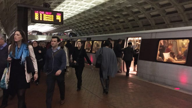 Commuters make their way through the Metro Center station in Washington, D.C.