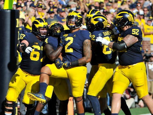 Teammates celebrate with Michigan tight end Devin Asiasi