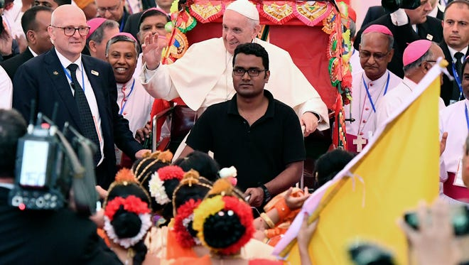 Pope Francis (C) arrives in a rickshaw at an Interreligious and Ecumenical meeting for peace at the garden of the Archbishop in Dhaka, Bangladesh.