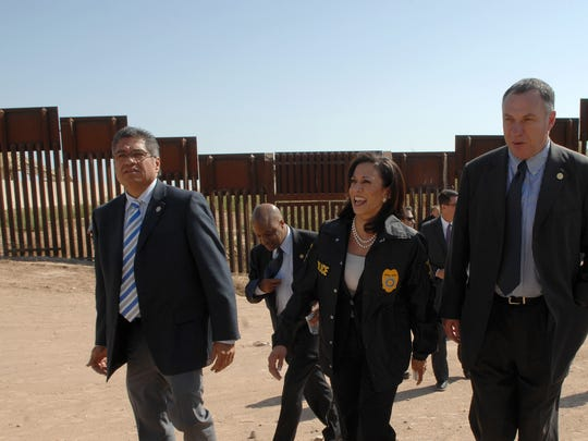 Imperial County District Attorney Gilbert Otero, left, visits the U.S.-Mexico border fence about 20 miles east of Calexico, Calif., on March 24, 2011. Otero was joined by California's then-Attorney General Kamala Harris, center.