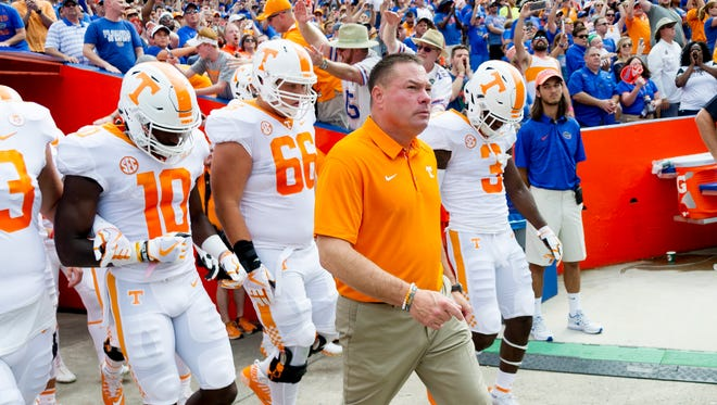Tennessee coach Butch Jones walks onto the field as the Vols get ready to face Florida at Ben Hill Griffin Stadium on Saturday, Sept. 16, 2017.