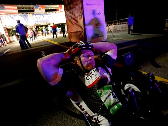 Travis Peruski of Linden, Michigan relaxes near the start finish line Runners head down West Fort Street to start the 40th Annual Detroit Free Press/Chemical Bank Marathon in Detroit, Michigan on Sunday, Oct 15, 2017.Peruski finished the marathon last year in fourth place and hoped to do even better with this years race.