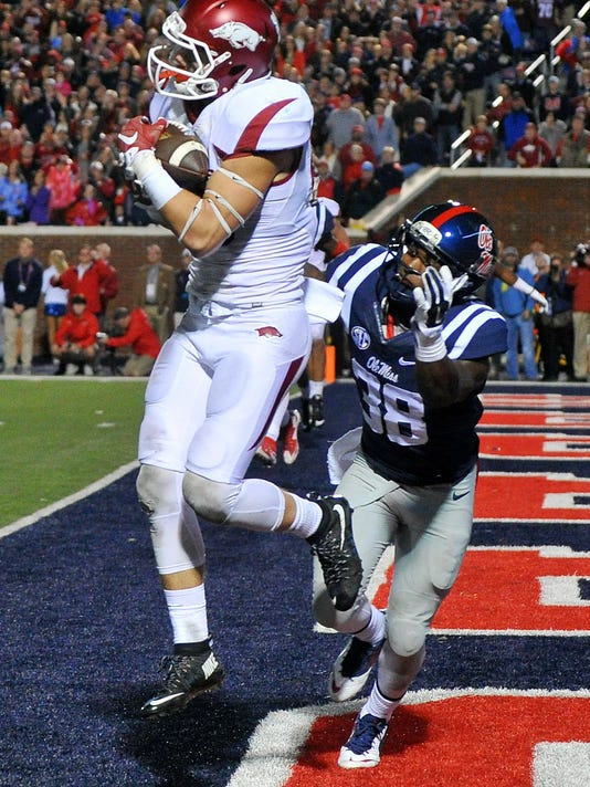 Arkansas wide receiver Drew Morgan, left, catches a pass over Mississippi defensive back Mike Hilton (38) during overtime of an NCAA college football game in Oxford, Miss., Saturday, Nov. 7, 2015. Arkansas won 53-52. (AP Photo/Thomas Graning)