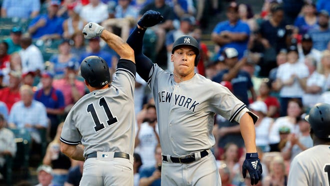 New York Yankees Brett Gardner (11) celebrates with Aaron Judge (99) after Judge hit a two-run home run against the Texas Rangers during the fifth inning of a baseball game Wednesday, May 23, 2018, in Arlington, Texas.