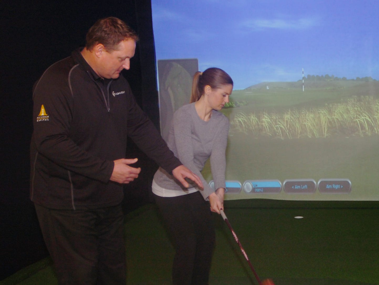 Bob Krause gives instruction to Libby Mikulich at the indoor golf facility in Birmingham.
