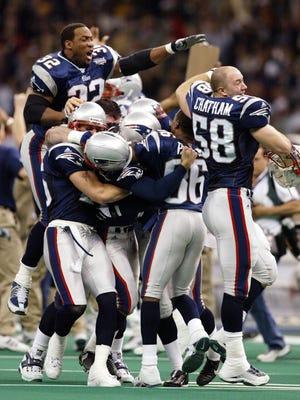 Patriots players celebrate their Super Bowl XXXVI upset of the Rams.