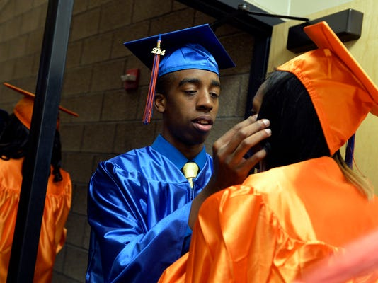 Jeshaun Maddox comforts classmate Symia Major-Kinard as they enter the auditorium for graduation at William Penn Senior High School in 2014.