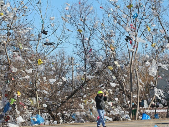 High winds scattered plastic trash bags from a suburban Milwaukee landfill into surrounding trees and fences in 2016.