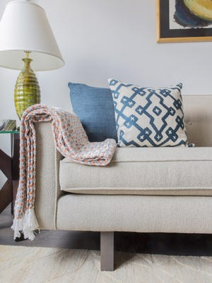 A patterned throw pops on a neutral sofa. Throws are an easy, low-commitment and cozy way to change the look of your home for fall.