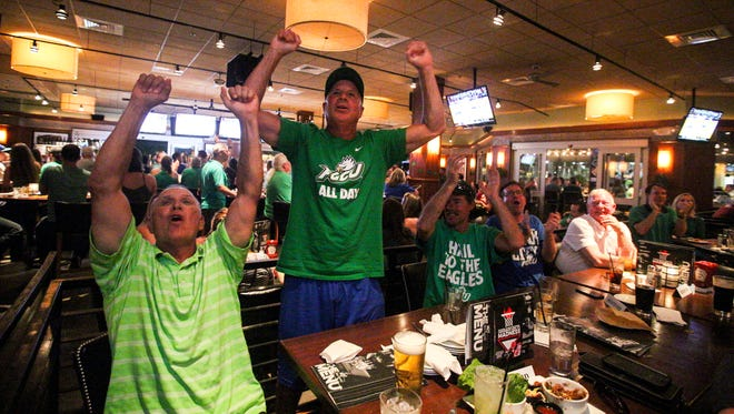 L to R - Steve Braun, Jeff Vitale, and Rich Wills are all big FGCU fans. They came out to the watch party at Bar Louie in the Gulf Coast Town Center to cheer on the Eagles in their game against North Carolina in the NCAA Tournament. They are reacting to a basket made by FGCU.