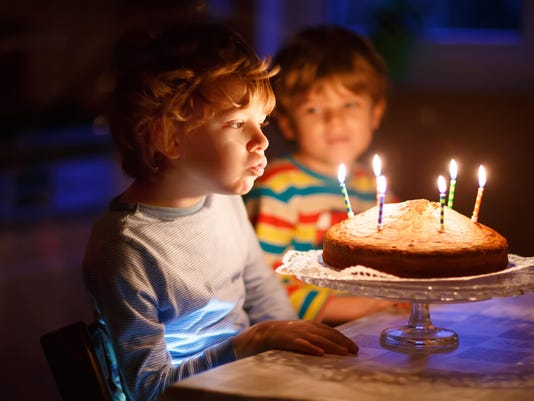 Little kid boy and brother blowing candles on birthday cake
