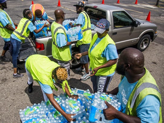 Tiondra Green, top left, places a case of bottled water onto the back of a pickup truck as her coworkers form a line to hand off cases of water,on Friday, Aug. 11, 2017, at Calvary Missionary Baptist Church in Flint, Mich.