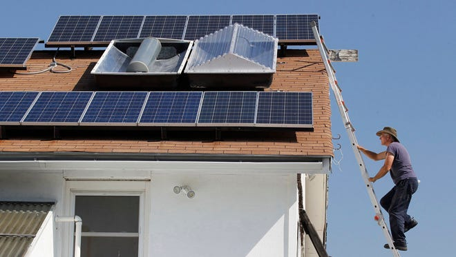 Mike Renner climbs onto the roof of his home in Weatherford, Texas, on Sept. 3, 2013, to service solar hot water and solar energy panels. Florida falls behind many states in solar power usage.