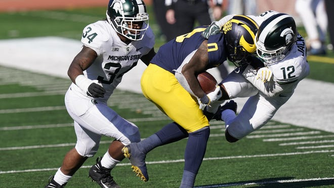 Michigan wide receiver Giles Jackson (0) is pulled out of bounds by Michigan State cornerback Chris Jackson (12) during the second half of an NCAA college football game, Saturday, Oct. 31, 2020, in Ann Arbor, Mich.