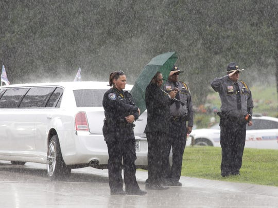 East Baton Rouge Sheriff's deputies salute during heavy rain Monday at the internment ceremony of Cpl. Montrell Jackson, one of three Baton Rouge law enforcement officers killed in a July 17 shootout in Baton Rouge.
