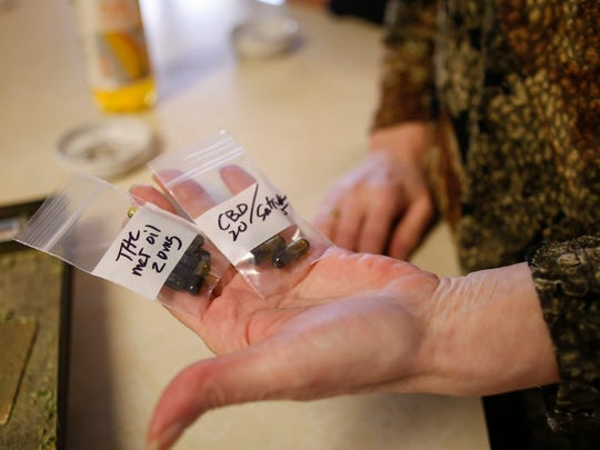 Dena Oyler, 58, of Grand Rapids, is a medical marijuana caregiver and patient, shows marijuana products she made to treat her own illnesses, which include multiple sclerosis, diabetes and others. She says the medicine has eased her symptoms.