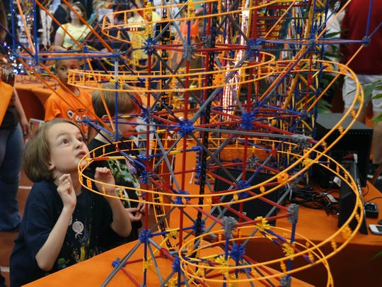 Evan Robey of Henrietta admires a spiral made of K'NEX pieces by students for Imagine RIT in 2016.