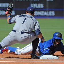 Toronto Blue Jays short stop Jose Reyes (7) dives safely back to first base ahead of the tag by Tampa Bay Rays first baseman Sean Rodriguez (1) at Rogers Centre.