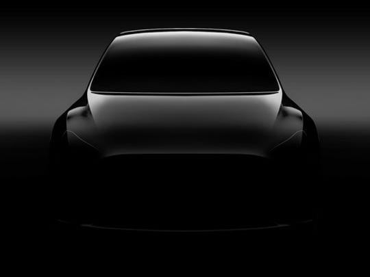 "A ""teaser"" photo of a silver Tesla Model Y, a sleek SUV, viewed from the front."