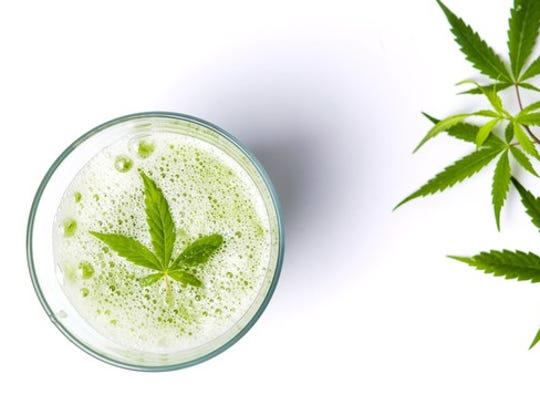Overhead view of a glass containing a beverage and a marijuana leaf next to a cannabis plant