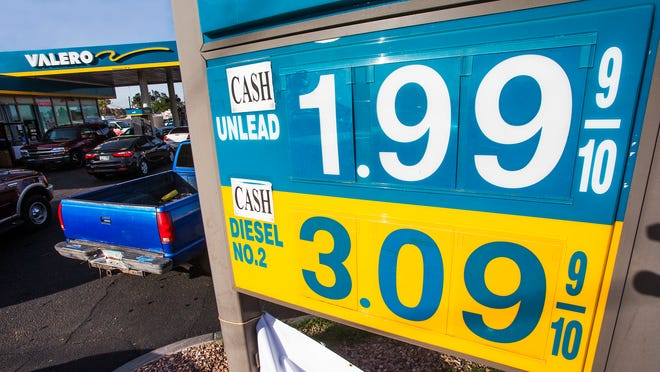 A couple dozen vehicles line up for $1.99 (cash) regular unleaded at the Valero gas station at 20th St. and Osborn in Phoenix, Monday morning, December 15, 2014. Prices are continuing to fall.