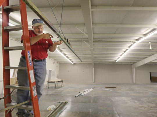 Don Johnson, co-owner, works on hanging runners at