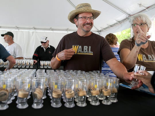 Curt and Diane Dawson of Bremerton hands out glasses with drink tokens at the 2016 BrewFest.