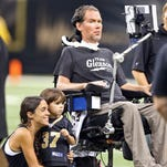 "In this image released by Open Road Films, former New Orleans Saints safety Steve Gleason, left, appears with his son Rivers, right, and wife Michel in a scene from the documentary ""Gleason."" The film follows Gleason and his wife, Michel, into the maelstrom of ALS, or Lou Gehrig's disease, as the couple adjusts to their fluctuating reality and makes way for their son, Rivers. (Open Road Films via AP)"