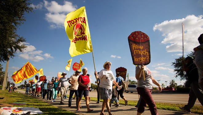Protestors march Sunday in front of the Wendy's restaurant on Daniels Parkway in south Fort Myers. The protest, led by the Coalition of Immokalee Workers, was held to call attention to the plight of farmworkers in Wendy's supply chain.