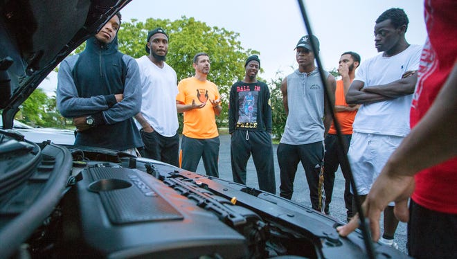 Ted Sottong, third from left, leads a car repair lesson recently for members of 'Pick Up The Ball'. PUTB is a mentorship program for young men in the Dunbar and East Fort Myers communities.