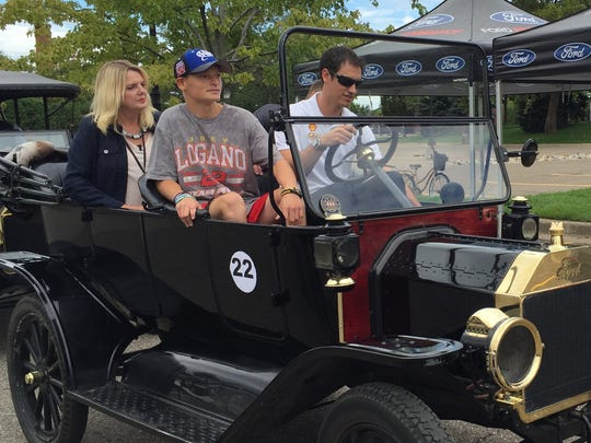 NASCAR driver Joey Logano, driving, and Make-a-Wish participant Randy Perry III take a spin in a Model T.