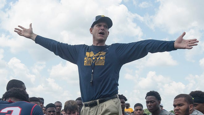 Michigan football coach Jim Harbaugh speaks to participants during a camp June 5, 2015, at Prattville High School in Prattville, Ala.