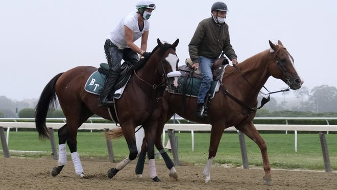 Belmont Stakes hopeful Robin Smullen on Tiz the Law, left, is led around the track by trainer Barclay Tagg during a workout at Belmont Park in Elmont, N.Y., Friday, June 19, 2020.