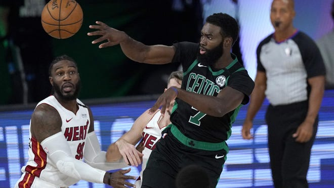 The Celtics' Jaylen Brown gets off a pass while being covered by the Heat's Jae Crowder, left, during the first half of Tuesday's Western Conference finals playoff game.