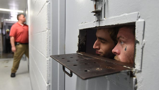 Inmates at the Marion County jail look out of their cell while jail administrator Russell Stockdale checks cells on Wednesday.