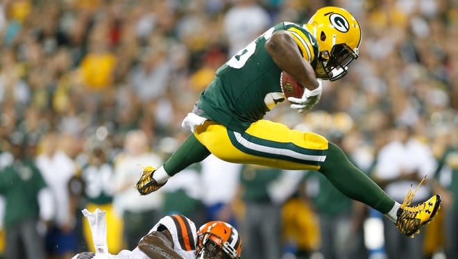 Green Bay Packers tight end Kennard Backman leaps over Cleveland Browns free safety Derrick Kindred.