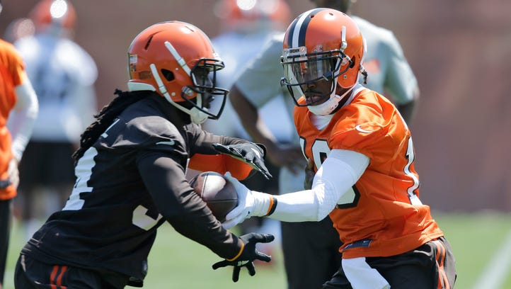 Cleveland Browns quarterback Robert Griffin III, right, hands the ball off to Cleveland Browns running back Isaiah Crowell during practice at the NFL football team's training camp facility, Wednesday, May 18, 2016, in Berea, Ohio. (AP Photo/Tony Dejak)