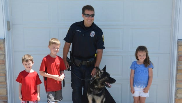 From left, Andrew Vorpahl, 4, Matthew Vorpahl, 8, Officer Chris Treml, Bax and Ava Vorpahl, 6. Matthew and his siblings donated $117.11 they raised at a lemonade stand to the Hobart-Lawrence Police Department's K-9 program.